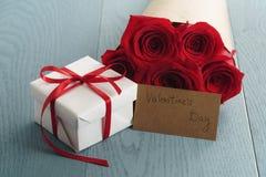 Boîte-cadeau avec le bouquet de roses rouges et carte de papier de jour de valentines sur la table en bois bleue Images libres de droits