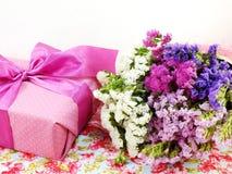 Boîte-cadeau avec le bouquet de ruban et de fleur sur le fond imprimé de tissu Photographie stock