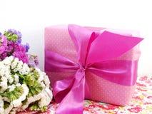 Boîte-cadeau avec le bouquet de ruban et de fleur sur le fond imprimé de tissu Photos libres de droits