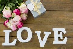 Boîte-cadeau avec le groupe de roses et l'alphabet d'amour sur la planche en bois Image stock