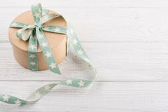 Boîte-cadeau avec le ruban d'étoile sur la table rustique blanche Images libres de droits