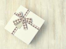 Boîte-cadeau avec le ruban dans une cage sur un fond en bois clair E Photo stock