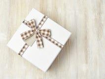 Boîte-cadeau avec le ruban dans une cage sur un fond en bois clair E Image stock