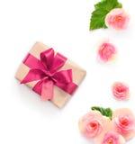 Boîte-cadeau avec le ruban rouge et arc sur le blanc avec le fond de fleurs lat plat, vue supérieure Photographie stock libre de droits