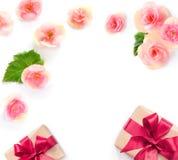 Boîte-cadeau avec le ruban rouge et arc sur le blanc avec le fond de fleurs lat plat, vue supérieure Photographie stock