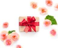 Boîte-cadeau avec le ruban rouge et arc sur le blanc avec le fond de fleurs lat plat, vue supérieure Image stock