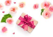 Boîte-cadeau avec le ruban rouge et arc sur le blanc avec le fond de fleurs lat plat, vue supérieure Images stock