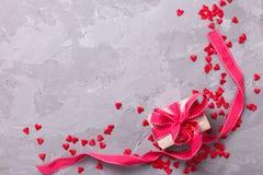 Boîte-cadeau avec le ruban rouge et beaucoup petit coeur rouge décoratif Image libre de droits