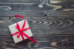 Boîte-cadeau avec le ruban rouge sur la table en bois Images stock