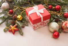 Boîte-cadeau avec les branches d'arbre de sapin et les boules décorées de Noël Image stock