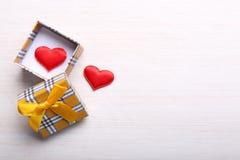 Boîte-cadeau avec les coeurs rouges sur le fond clair Photos libres de droits