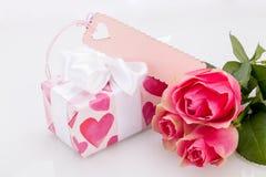 Boîte-cadeau avec un Empty tag, à côté de trois roses Photo libre de droits
