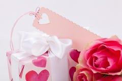 Boîte-cadeau avec un Empty tag, à côté de trois roses Photo stock