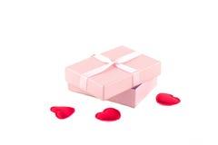 Boîte-cadeau avec un ruban rose et des coeurs rouges Images stock