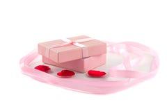 Boîte-cadeau avec un ruban rose et des coeurs rouges et un a Photos stock