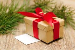 Boîte-cadeau beige avec le ruban rouge au foyer mou Photo stock