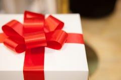 Boîte-cadeau blanc attaché avec le ruban rouge élégant Images stock