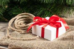 Boîte-cadeau blanc avec les rubans, la branche d'arbre de cristmas et la corde rouges o Images libres de droits