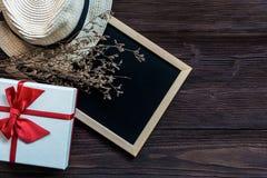Boîte-cadeau blanc de Saint Valentin avec le chapeau et la fleur près du conseil pour des couples de surprise, photo stock