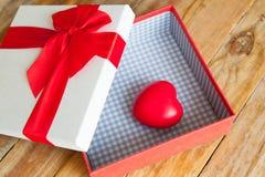 Boîte-cadeau blanc et coeur de ruban et mini rouge à l'intérieur sur le dos en bois Photo libre de droits