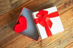 Boîte-cadeau blanc et coeur de ruban et mini rouge à l'intérieur sur le dos en bois Photos stock
