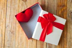 Boîte-cadeau blanc et coeur de ruban et mini rouge à l'intérieur sur le dos en bois Images stock