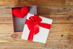 Boîte-cadeau blanc et coeur de ruban et mini rouge à l'intérieur sur le dos en bois Photo stock