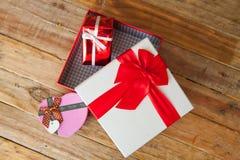 Boîte-cadeau blanc et coeur de ruban et mini rouge à l'intérieur sur le dos en bois Photographie stock libre de droits