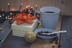 Boîte-cadeau blanc, tasse bleue, grains de café dans une cuvette, ballnn d'or Images stock