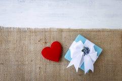 Boîte-cadeau bleu avec le coeur rouge sur le tissu hessois Image libre de droits
