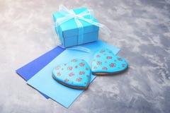 Boîte-cadeau bleu, deux enveloppes et pain d'épice de deux coeurs sur le fond concret Images stock