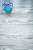 Boîte-cadeau bleu en forme de coeur avec le ruban rose sur le cele de conseil en bois Photos libres de droits