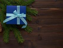 Boîte-cadeau bleu-foncé de Noël attaché avec le ruban de turquoise sur le spruc Image stock