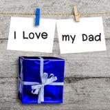 Boîte-cadeau bleu sur le mur en bois avec un papier blanc Photo libre de droits