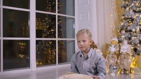 Boîte-cadeau blond de christmass de jet de garçon sur le fond d'arbre de christmass clips vidéos