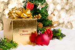 Boîte-cadeau brillant d'or avec le mot de Joyeux Noël avec le decoratio rouge Images stock