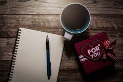 Boîte-cadeau, carnet, stylo et café sur la planche en bois Images libres de droits