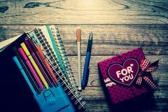 Boîte-cadeau, carnets et stylos sur la planche en bois Photos stock