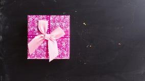 Boîte-cadeau carré rose sur la configuration d'appartement de fond de panneau de craie Photos libres de droits