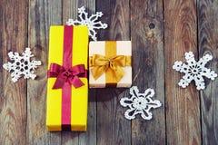 Boîte-cadeau colorés avec des arcs et flocons de neige au-dessus de backgr en bois Photographie stock libre de droits