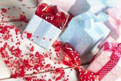 Boîte-cadeau colorés et coeurs rouges sur les planches en bois Image stock