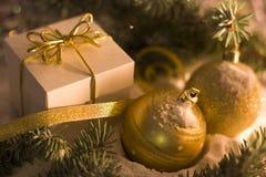 Boîte-cadeau d'or avec l'arc argenté, boules de jouet image stock
