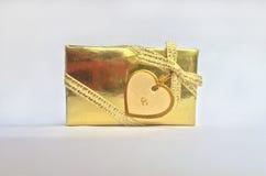 Boîte-cadeau d'or avec la carte de label de coeur Photographie stock libre de droits