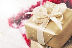 Boîte-cadeau d'or avec le beaux ruban et arc sur un fond brillant lumineux Image stock
