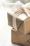 Boîte-cadeau d'or avec le beaux ruban et arc sur un fond brillant lumineux Photo libre de droits