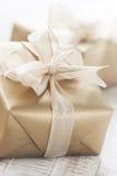Boîte-cadeau d'or avec le beaux ruban et arc sur un tibia lumineux Photos libres de droits