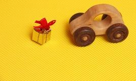Boîte-cadeau d'or avec le ruban rouge devant le jouet en bois de voiture sur le fond jaune diagonal ondulé, souvenir pour le jour photographie stock