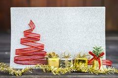 Boîte-cadeau d'or et d'argent avec la décoration de Noël au-dessus du fond argenté brouillé de papier de scintillement photo libre de droits