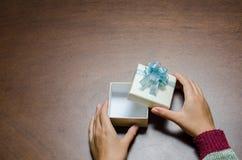 Boîte-cadeau d'ouverture de main sur le fond en bois Photo libre de droits