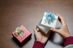 Boîte-cadeau d'ouverture de main sur le fond en bois Image stock